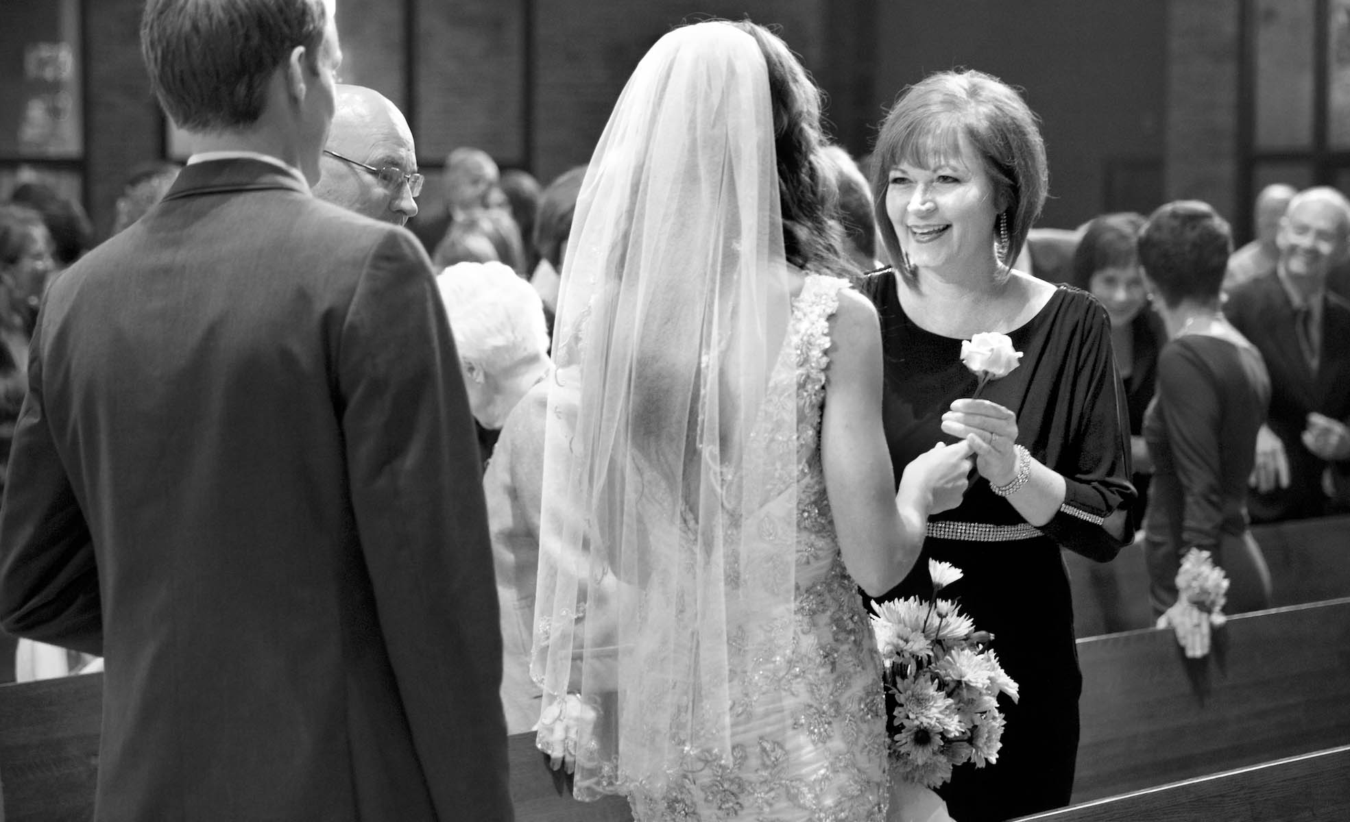 Alissa gives a flower to her mother during the sign of peace, ceremony at Our Saviour Catholic Church, Jacksonville. Wedding photography by Tiffany & Steve Warmowski.