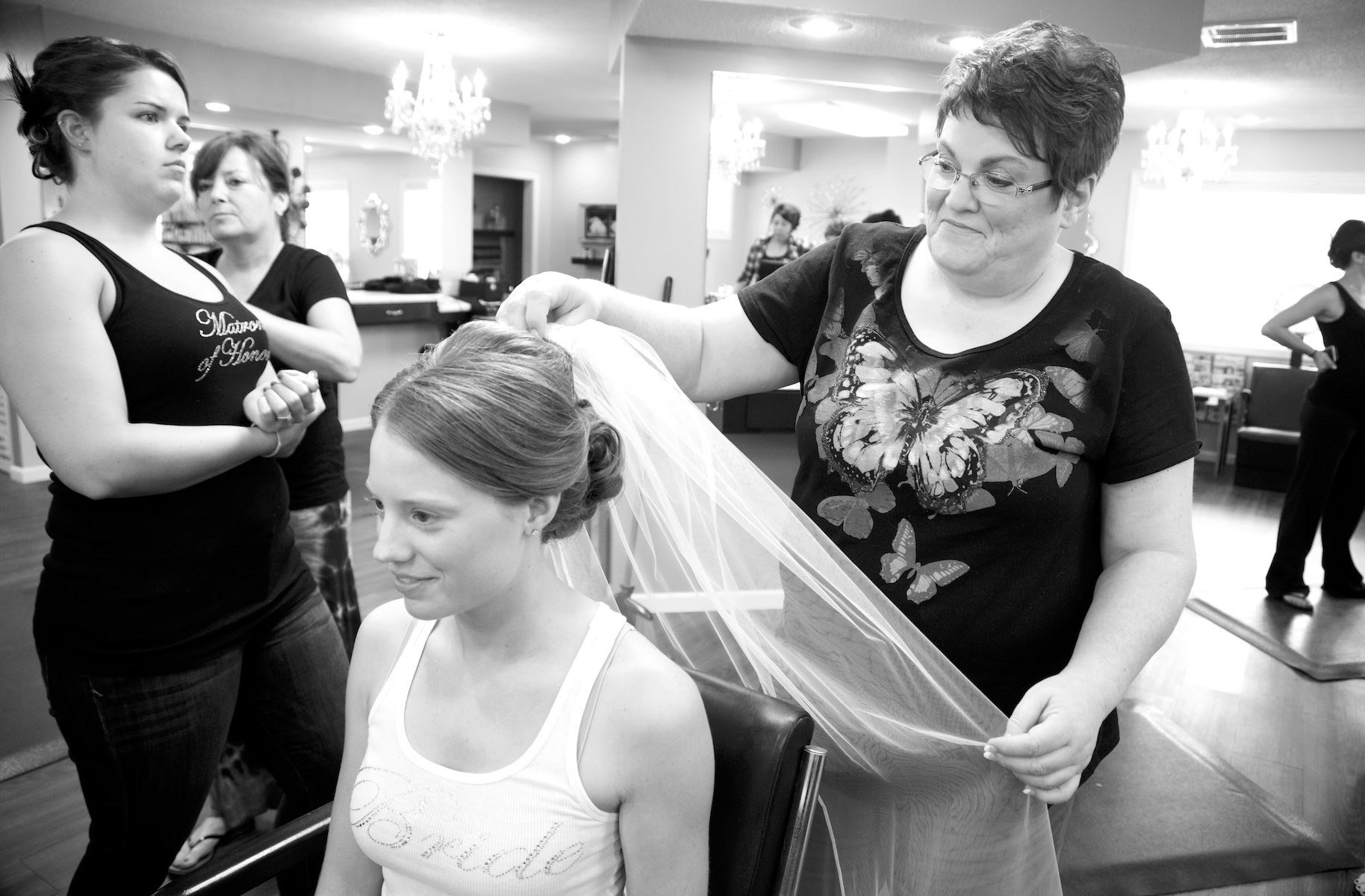 Amanda's mom fastens the veil as Amanda and her bridesmaids get ready at A Hair Company beauty salon in Jacksonville. Wedding photography by Steve & Tiffany Warmowski.