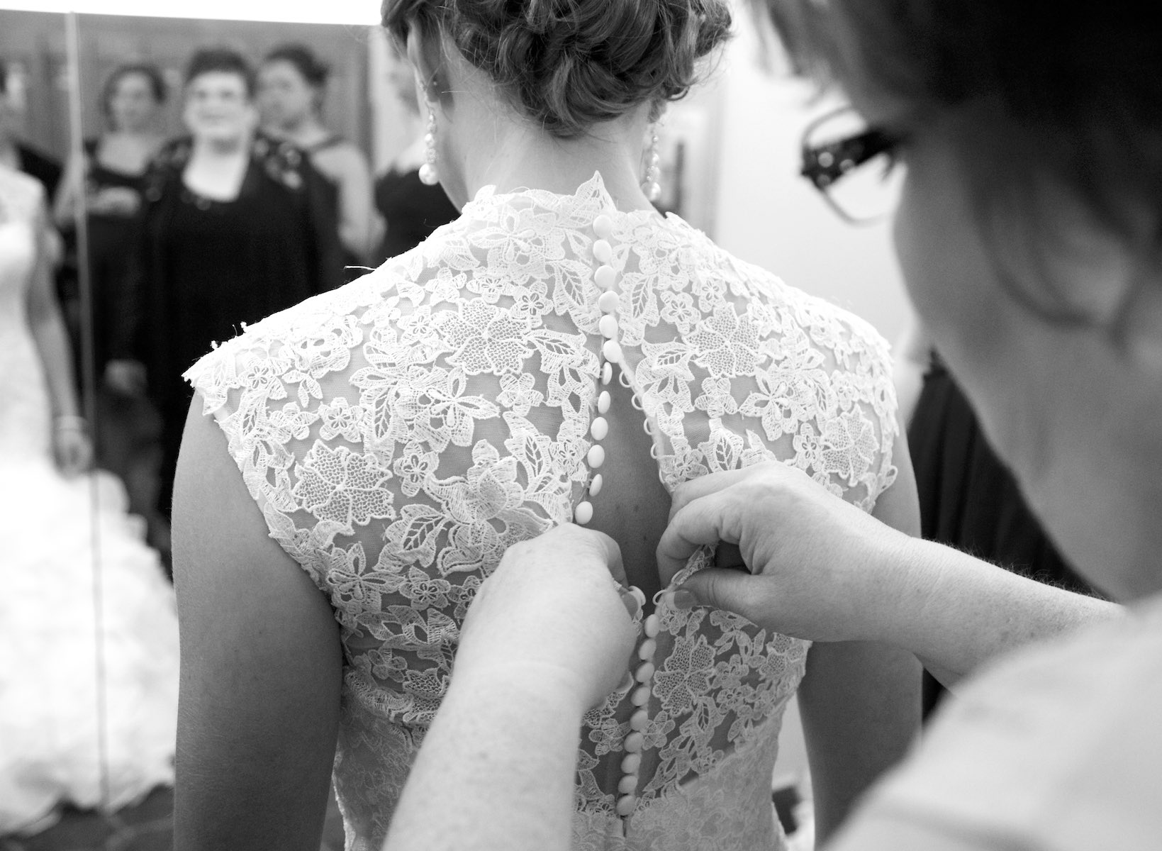 Close family friend Sharon buttons up the dress at the Jacksonville Country Club. Wedding photography by Steve & Tiffany Warmowski.