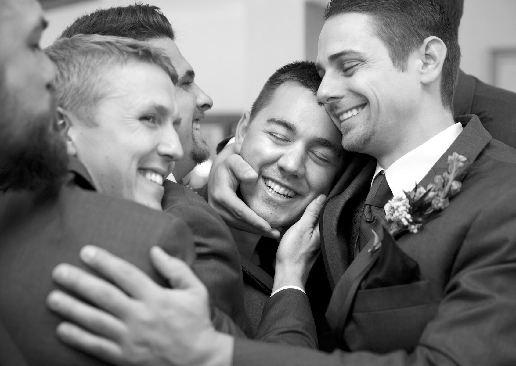 Nick gets a group hug from his attendants as they get ready for the wedding ceremony at the Jacksonville Illinois Country Club. Wedding photography by Steve & Tiffany Warmowski