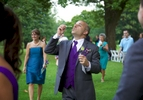 Nick's father blows bubbles after the outdoor wedding ceremony at the Jacksonville Illinois Country Club. Wedding photography by Steve & Tiffany Warmowski.