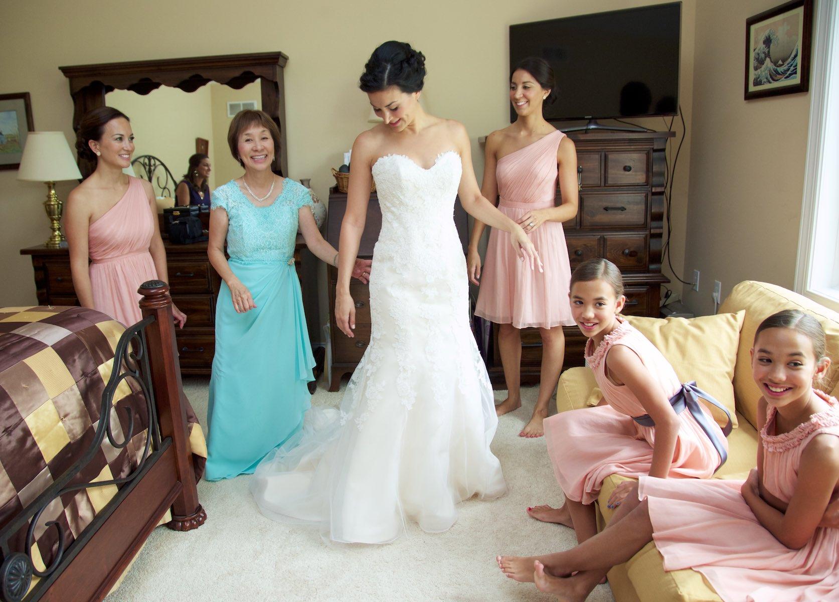 Putting on dress, Emi & Daniel's wedding in Lake Geneva, Wisconsin. Wedding photography by Steve & Tiffany Warmowski.
