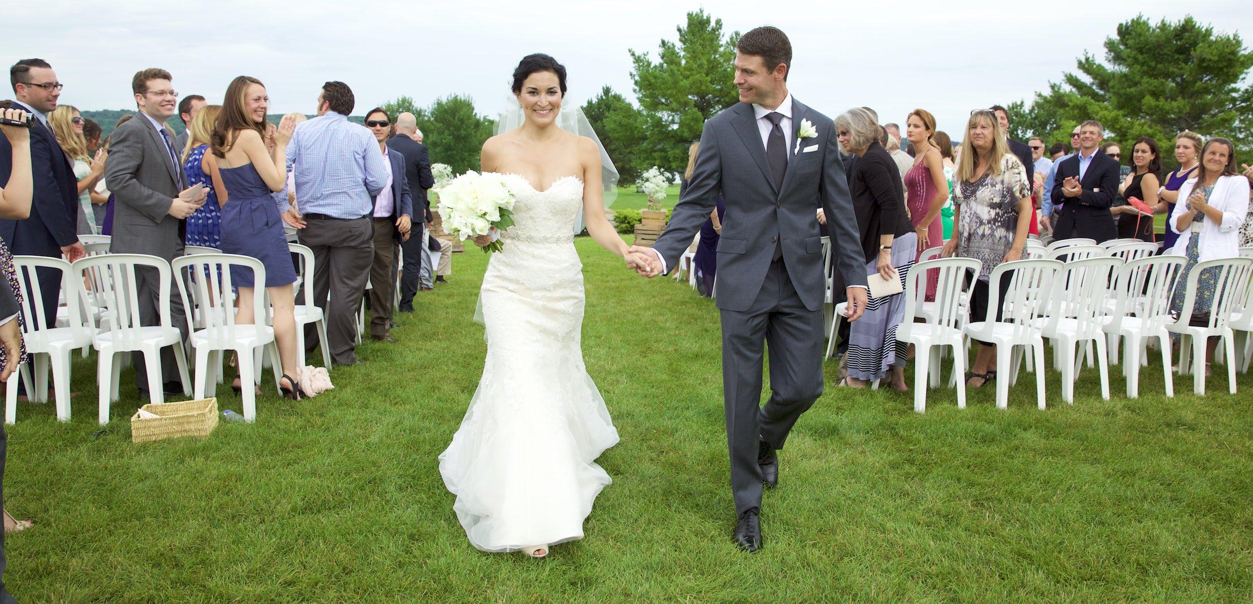Bride and groom come down the aisle, Emi & Daniel's wedding ceremony at Geneva National Golf Club in Lake Geneva, Wisconsin. Wedding photography by Steve & Tiffany Warmowski.