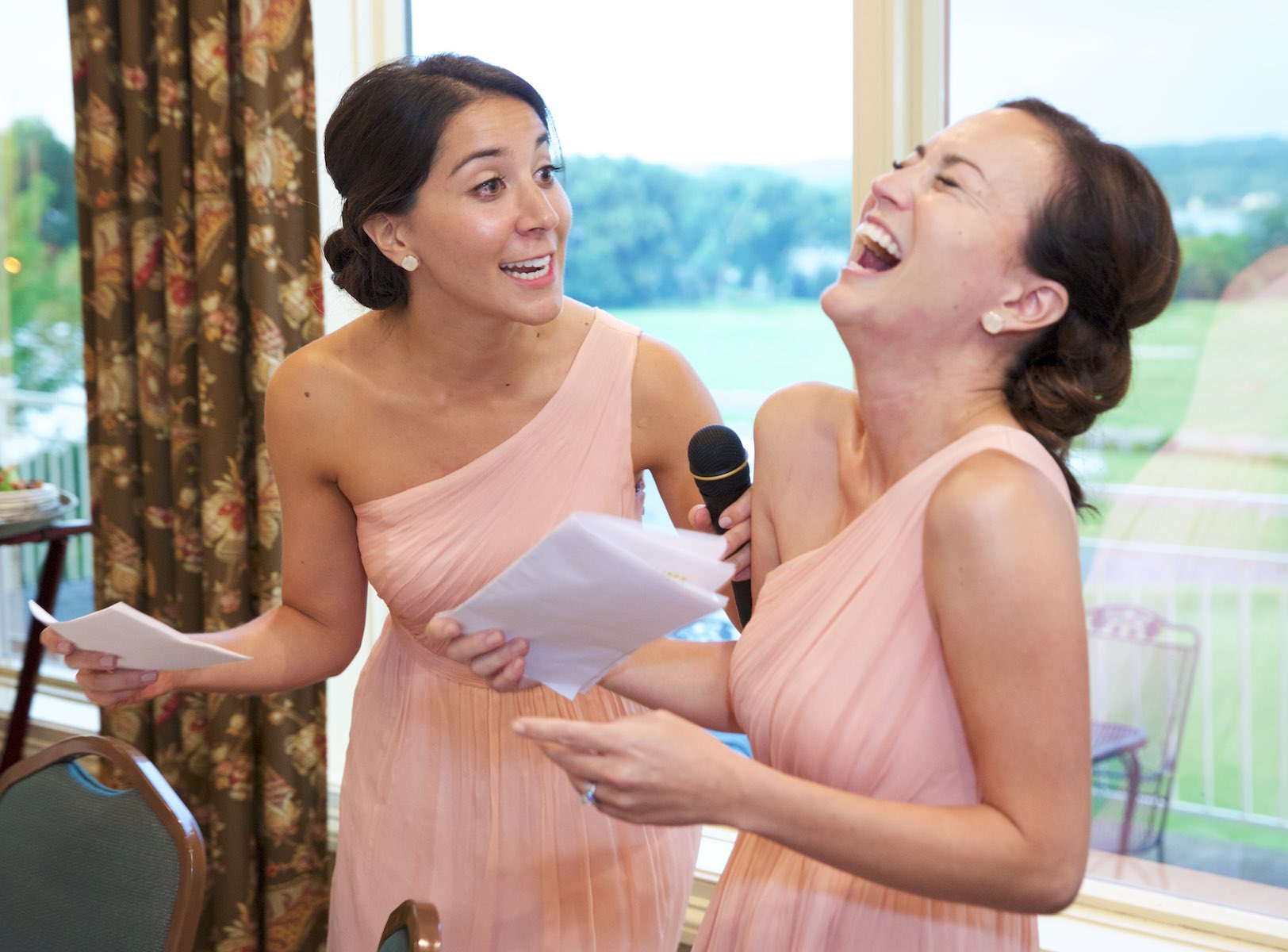 Emi's sisters laugh during their toast and speech, wedding at Geneva National Golf Club in Lake Geneva, Wisconsin. Wedding photography by Steve & Tiffany Warmowski.