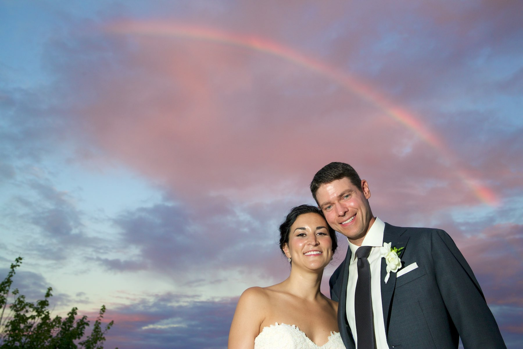 Reacting to a rainbow at sunset, a quick portrait of Emi & Daniel on balcony during wedding reception at Geneva National Golf Club in Lake Geneva, Wisconsin. Wedding photography by Steve & Tiffany Warmowski.