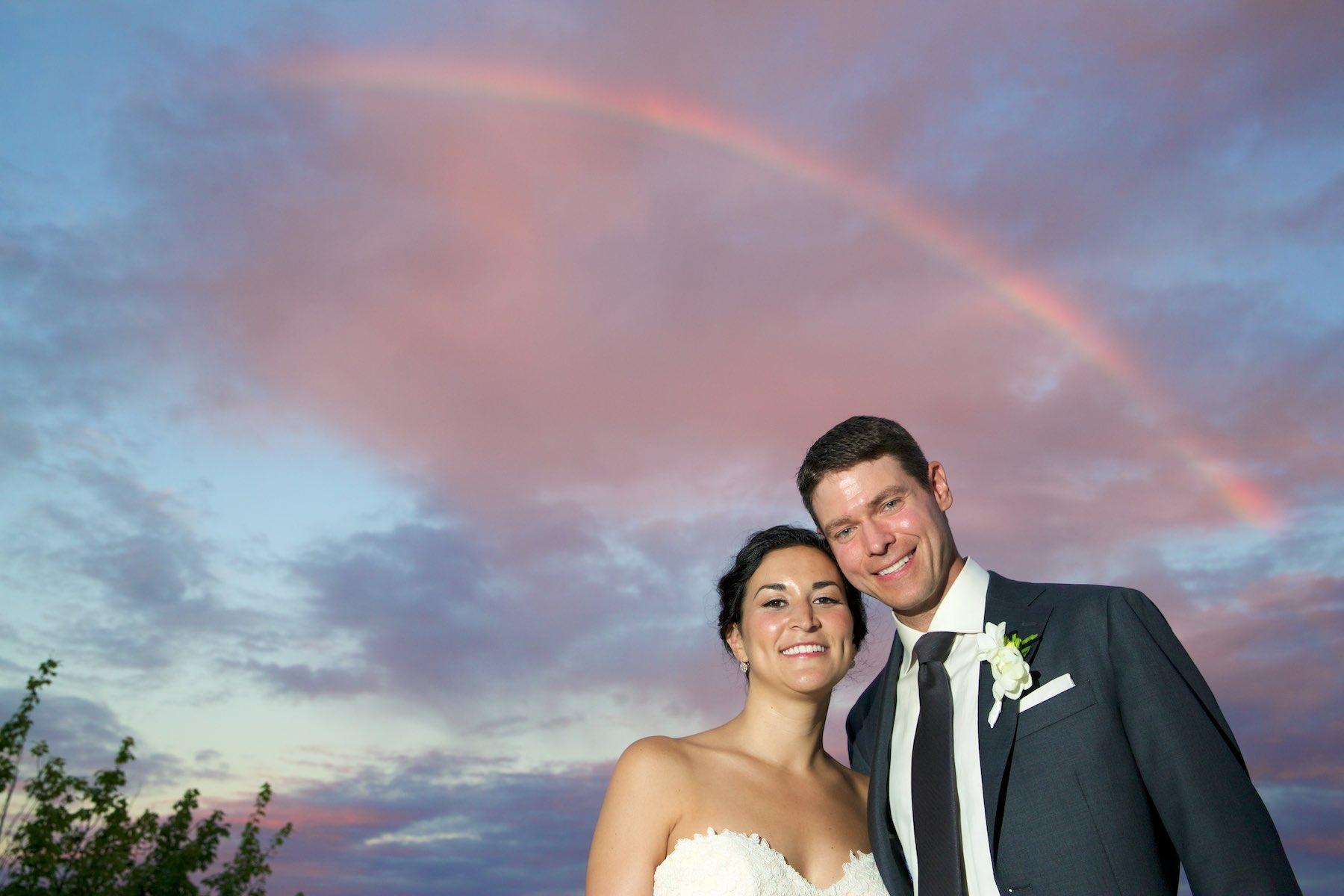 Reacting to a rainbow at sunset, a quick portrait of Emi & Daniel on balcony during wedding reception at Geneva National Golf Club in Lake Geneva, Wisconsin. Wedding photography by Steve & Tiffany Warmowski.
