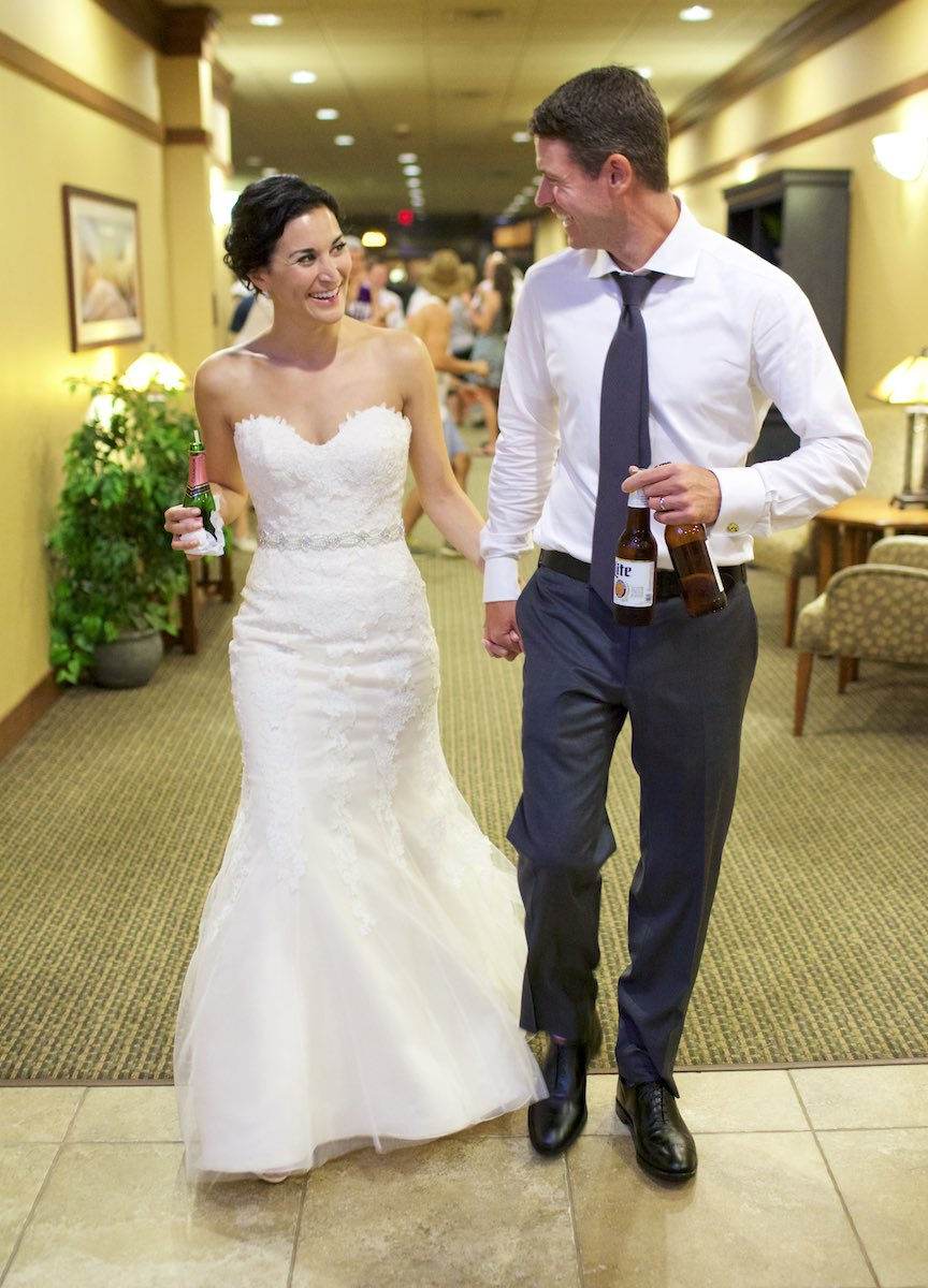 After the reception, Emi and Daniel lead friends to the hotel bar, Geneva National Resort in Lake Geneva, Wisconsin. Wedding photography by Steve & Tiffany Warmowski.