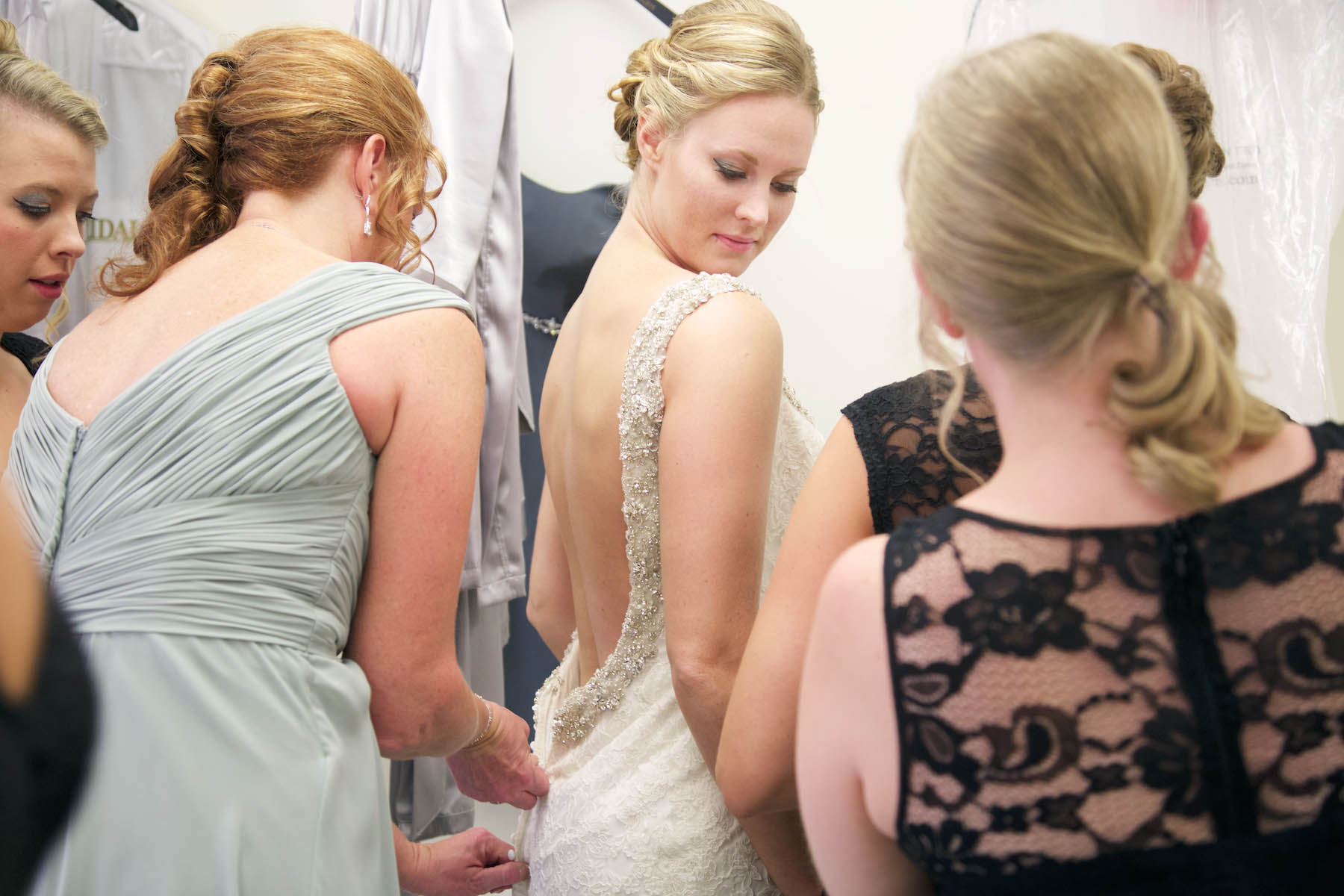Jaclyn's mom helps her with her dress before the ceremony at Allerton Park, Monticello. Wedding photography by Tiffany & Steve of Warmowski Photography.