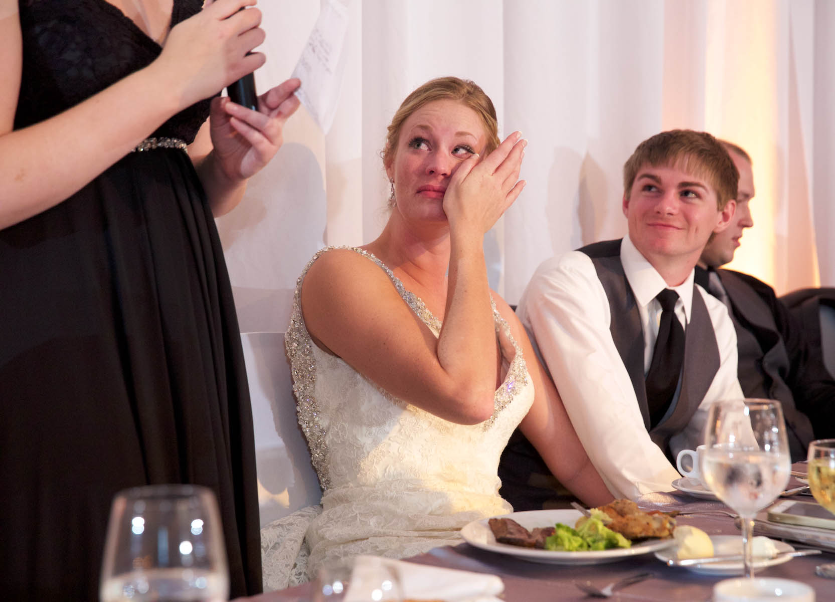 Jaclyn reacts to a toast from her sister (and maid of honor) during the wedding reception at iHotel, Champaign. Wedding photography by Tiffany & Steve of Warmowski Photography.