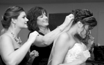 Adria gets help from her mother and sister as she she gets ready in the basement bridal room at Annie Merner Chapel,  MacMurray College, Jacksonville, Illinois. Wedding photography by Steve & Tiffany Warmowski.