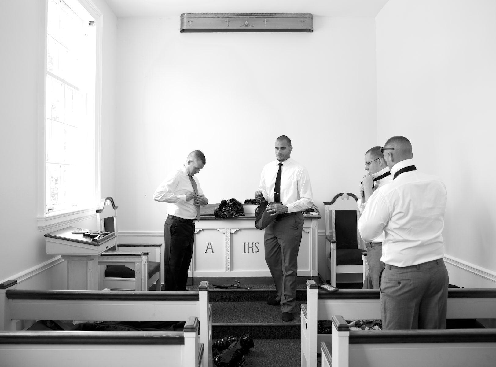 Jeremy and his groomsmen get dressed in the small chapel at MacMurray College's Annie Merner Chapel in Jacksonville, Illinois. Wedding photography by Steve & Tiffany Warmowski.