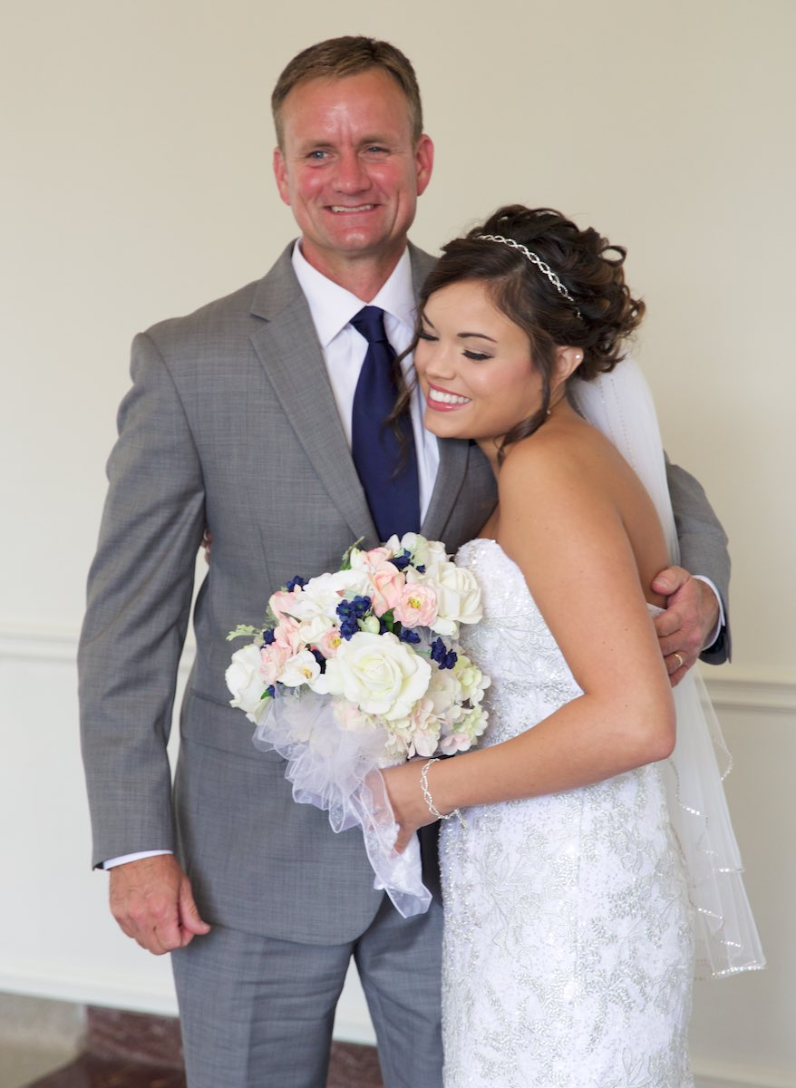 Adria gets a hug from her father after he saw her for the first time in his wedding dress. We ofter do {quote}first looks{quote} for the bride and groom, but Adria wanted to have that special moment with her father as well. Wedding photography by Steve & Tiffany Warmowski.