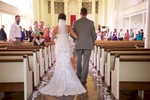 Adria walks with her father down the large center aisle at Annie Merner Chapel, MacMurray College, Jacksonville, Illinois. Wedding photography by Steve & Tiffany Warmowski.
