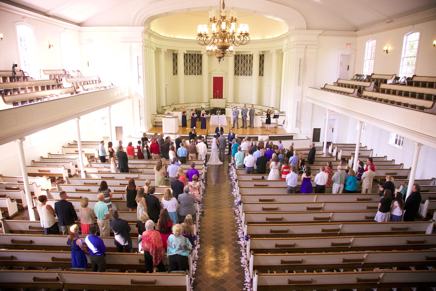 Overall photo shows those in attendance and decorations at Annie Merner Chapel, MacMurray College, Jacksonville, Illinois. Wedding photography by Steve & Tiffany Warmowski.