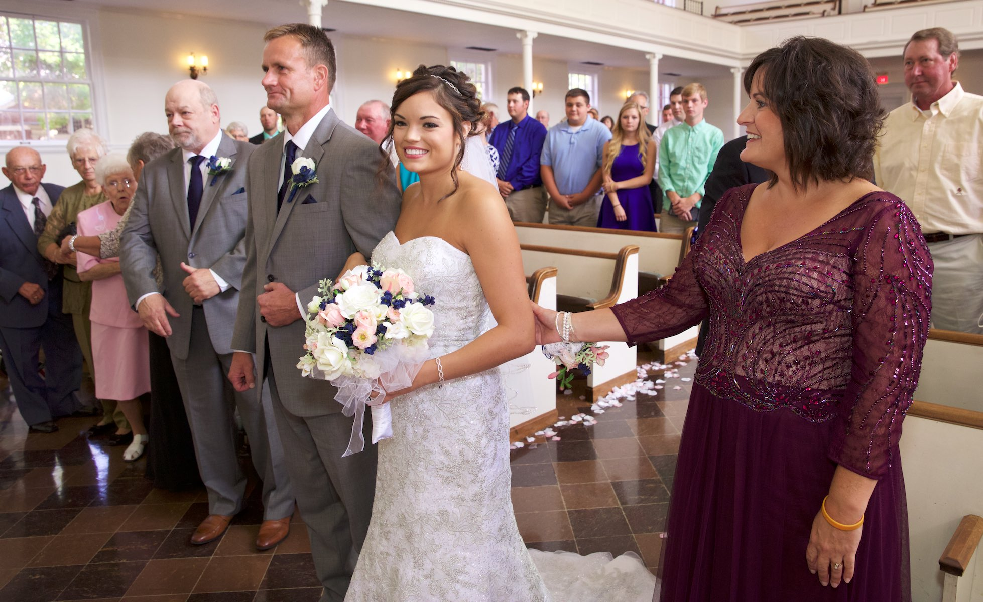 Adria shares a moment with her mom during the start of the wedding ceremony, Annie Merner Chapel, MacMurray College, Jacksonville, Illinois. Wedding photography by Steve & Tiffany Warmowski.