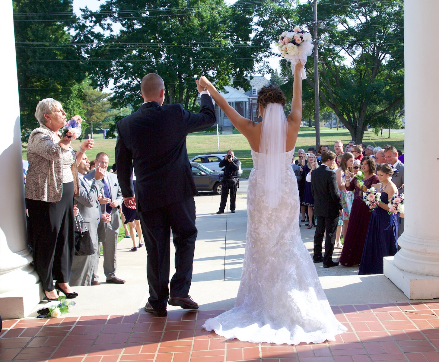 Adria and Jeremy greeted by bubbles, Annie Merner Chapel, MacMurray College, Jacksonville, Illinois. Wedding photography by Steve & Tiffany Warmowski.