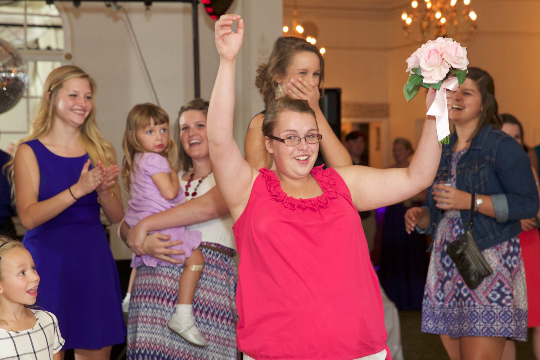 Catching the bouquet, bouquet toss, wedding reception at Hamilton's 110 North East, Jacksonville, Illinois. Wedding photography by Steve & Tiffany Warmowski.