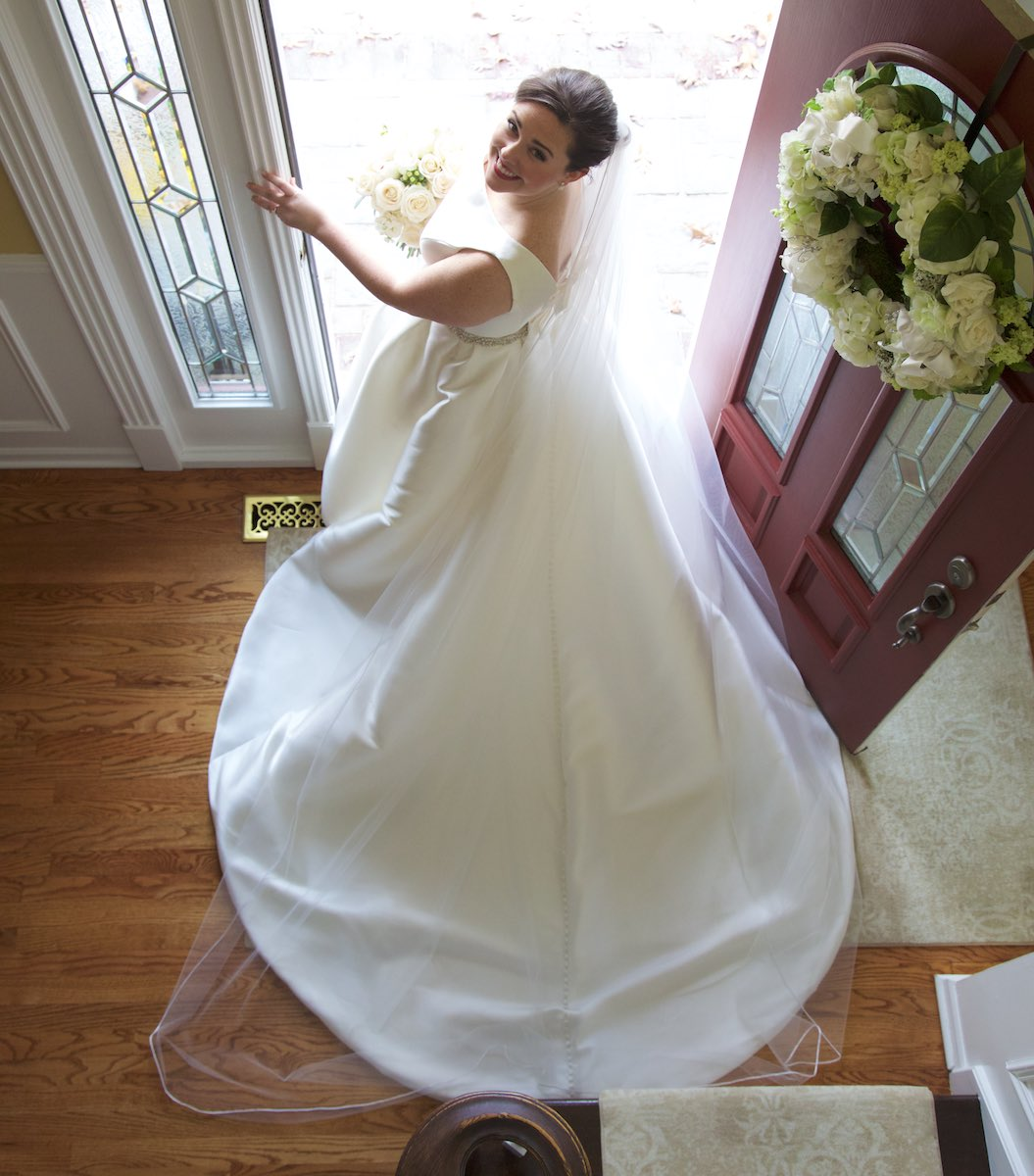 Elizabeth poses in the doorway of the house she grew up in, before heading to the ceremony at St. Rita of Cascia Shrine Chapel in Chicago. Wedding photography by Steve & Tiffany Warmowski