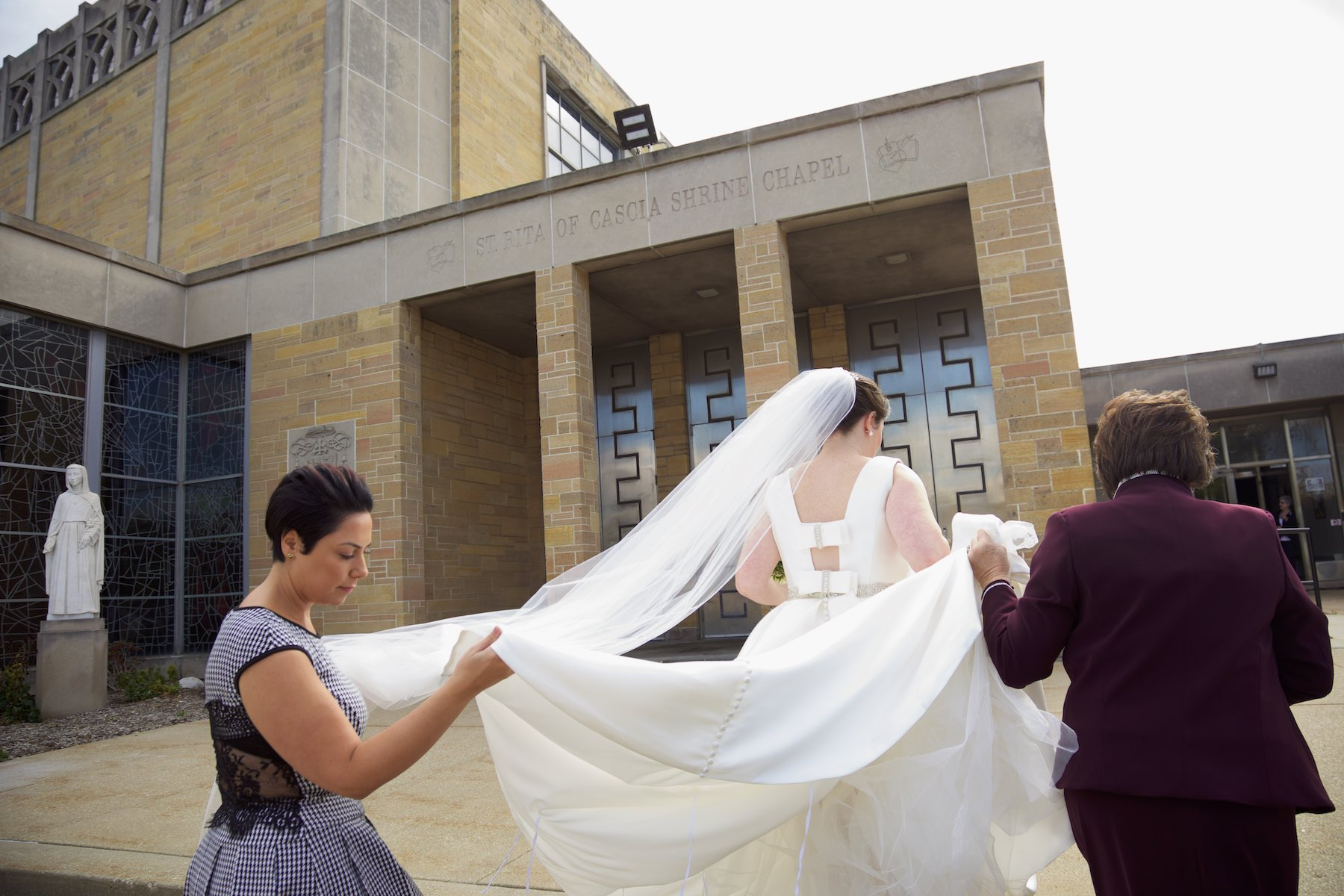 Elizabeth arrives at St. Rita of Cascia Shrine Chapel in Chicago for the ceremony. Wedding photography by Steve & Tiffany Warmowski