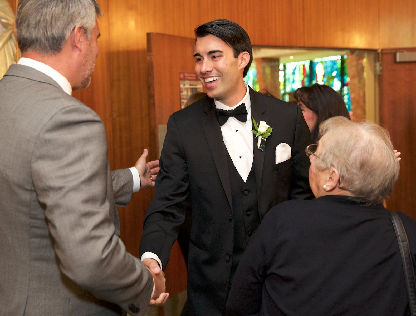 Daniel greets guests before the start of the ceremony at St. Rita of Cascia Shrine Chapel in Chicago. Wedding photography by Steve & Tiffany Warmowski