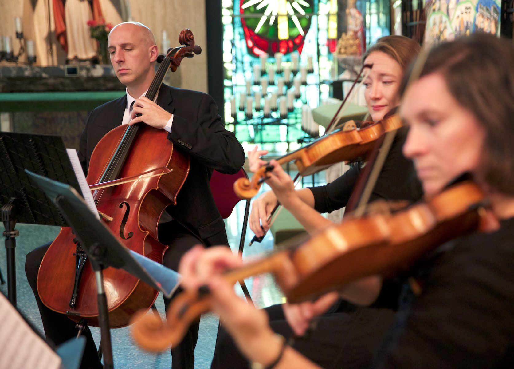 Musicians fill St. Rita of Cascia Shrine Chapel in Chicago with wedding music before the ceremony. Wedding photography by Steve & Tiffany Warmowski