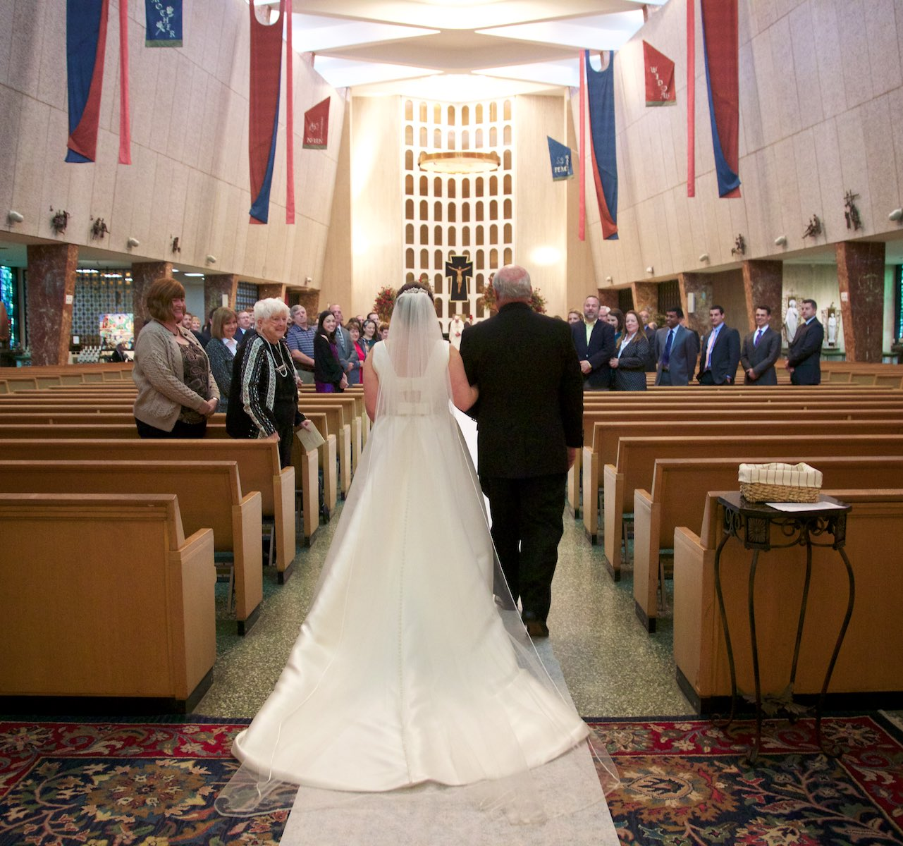 Elizabeth and her father walks down the aisle, St. Rita of Cascia Shrine Chapel in Chicago. St. Rita High School took over from a seminary preparatory institution, so the school has a larger and more beautiful chapel than expected. Wedding photography by Steve & Tiffany Warmowski