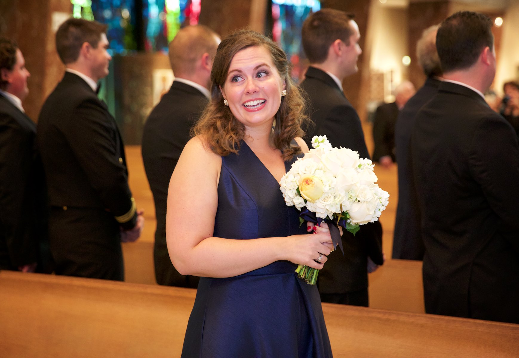 Daniel's sister (and his honor attendant) watches as her brother reacts to the bride coming down the aisle, ceremony at St. Rita of Cascia Shrine Chapel in Chicago. Wedding photography by Steve & Tiffany Warmowski