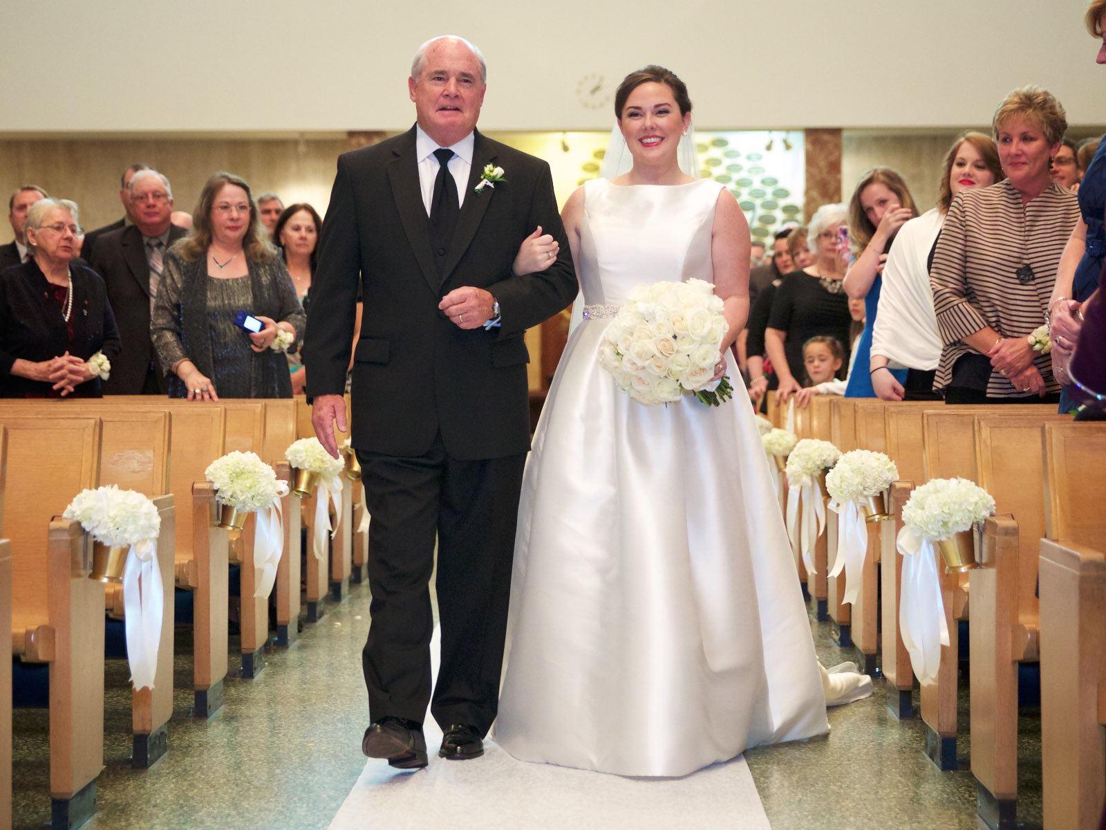 Elizabeth walks down the aisle with her father, ceremony at St. Rita of Cascia Shrine Chapel in Chicago. Wedding photography by Steve & Tiffany Warmowski