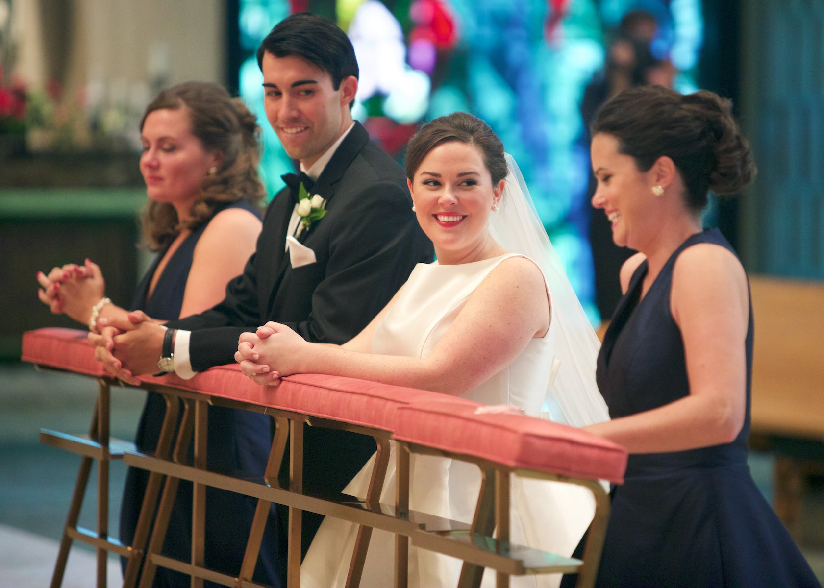 Elizabeth shares a moment with her sister, wedding ceremony at St. Rita of Cascia Shrine Chapel in Chicago. Wedding photography by Steve & Tiffany Warmowski
