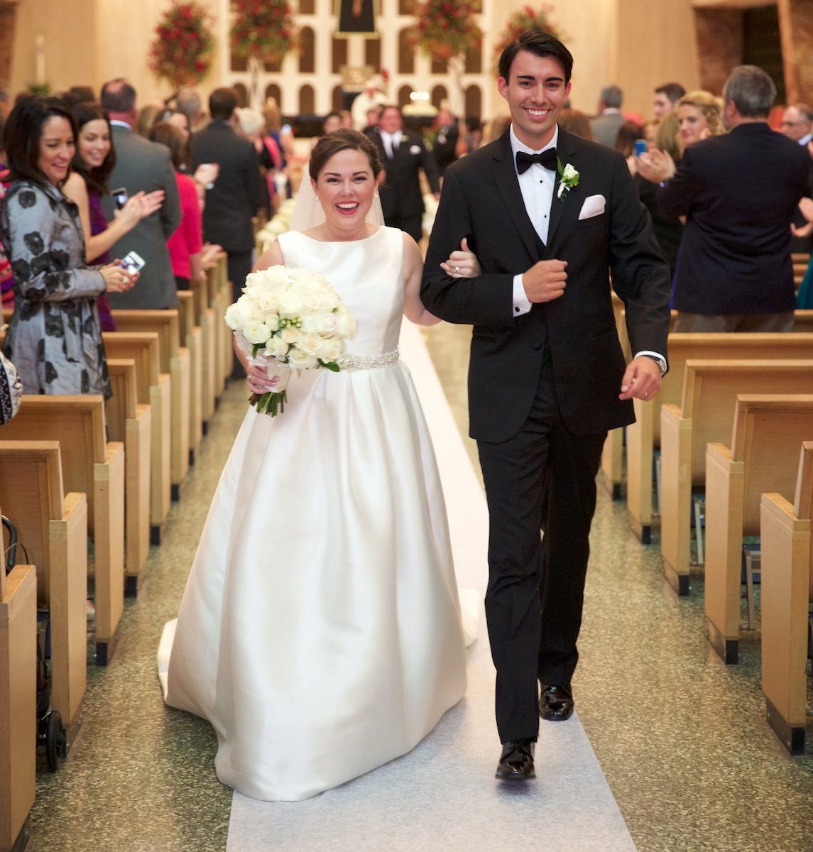 Elizabeth & Daniel walk down the aisle together at the end of the wedding ceremony at St. Rita of Cascia Shrine Chapel in Chicago. Wedding photography by Steve & Tiffany Warmowski