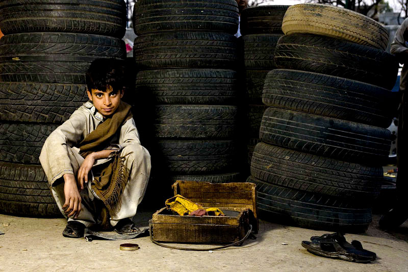 Shoe Shine boy, working outside the auto and tire shops behind Super Market area, Islamabad