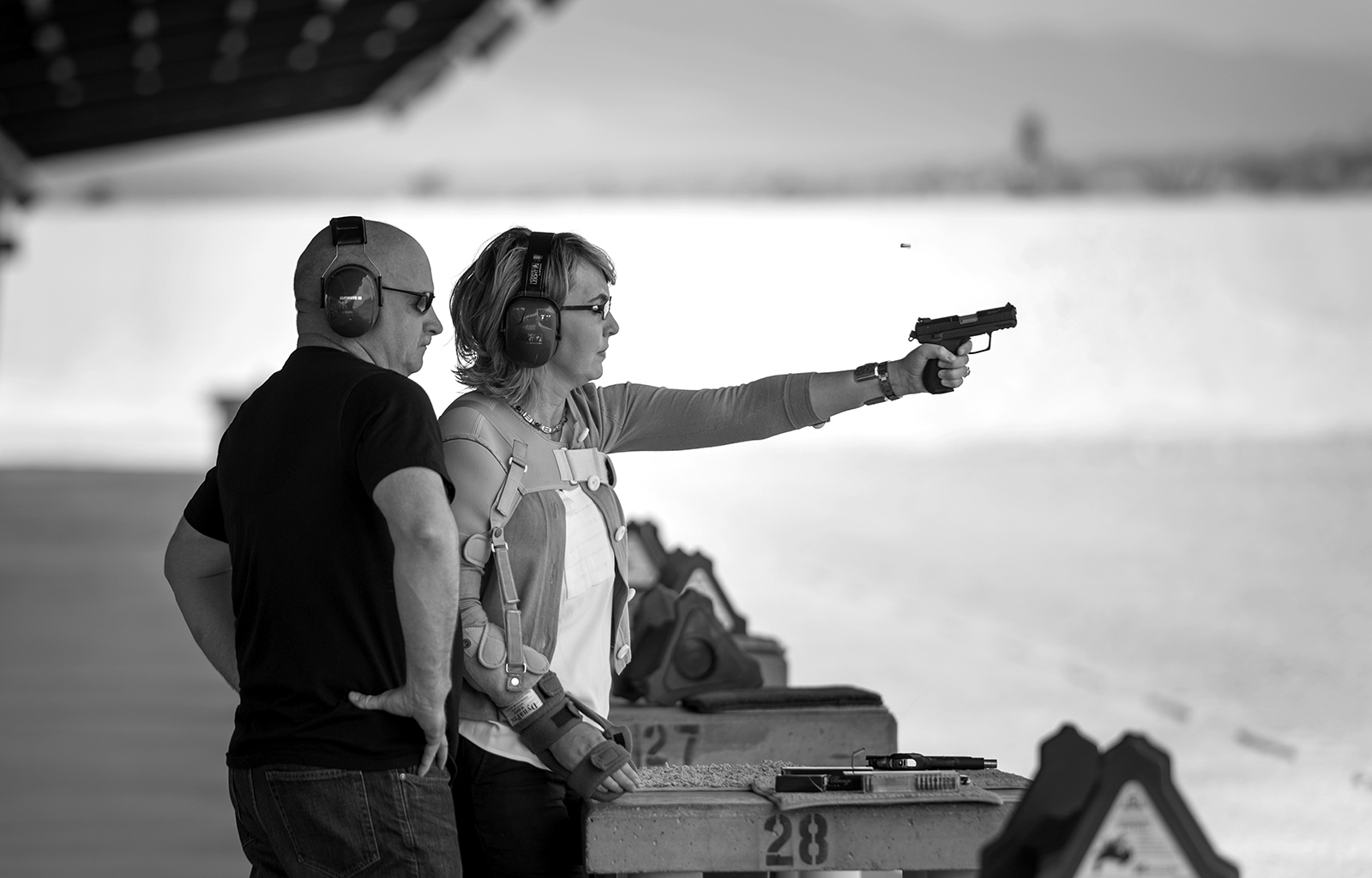 With steely determination former U.S. Representative Gabrielle Giffords fires a gun for the first time since being shot in the head during a meet and greet with constituents in Arizona more than 2 years ago as her husband Mark Kelly watches  on Monday, July 1, 2013. © 2013 Nikki Kahn/The Washington Post ALL RIGHTS RESERVED