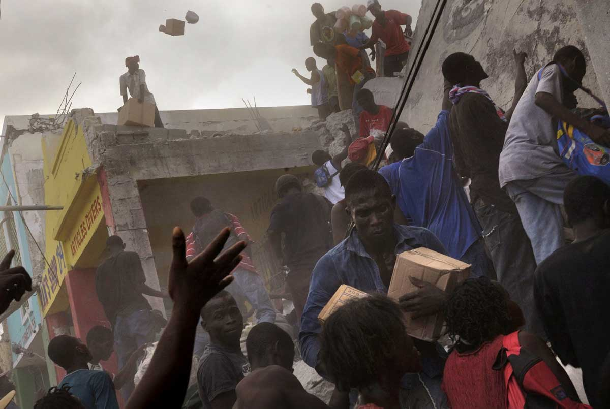 Following days without food or water, earthquake survivors take goods from a store on the main commerce street in  Port-Au-Prince as dust filled the air.  Police would come to control the crowd but within minutes they would return to scavenge for items.© Nikki Kahn/The Washington Post 2010ALL RIGHTS RESERVED