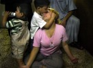 Halla gets a kiss from her son Iaad Hameed, 4, while her two year-old drinks from a bottle. Halla's husband, the father of her two children, was killed in the violence surrounding Baghdad during the initial days of the U.S. invasion in Iraq. (photo by Andrea Bruce/The Washington Post)