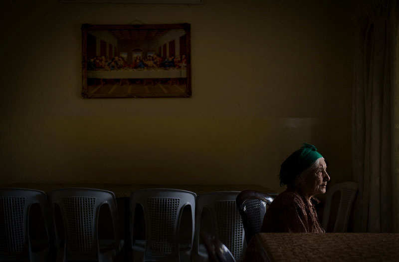 Doris Yunan sits in the empty dining room where the sun can find her. With help from the wind, shapes and shadows tease her from the picture window. The sun winks at her from behind a bowing date palm. The light creates a sensation that, sometimes, she says, overcomes her blindness.Doris, 83, sits in her regular spot especially when she prays. Arabic romance movies play in the next room, keeping the attention of 14 other elderly women who live at Beit Anya, a charity home in Baghdad run by Christians.The home takes in women left abandoned by death or family or war. Most are old, some are handicapped. Before the war, when the home was opened, there were only four women living there. Now there are 47.{quote}When it hurts, I can't see anything,{quote} Doris says. {quote}But now it is not hurting me, so I can see a little.{quote}Eve Peters, a 21-year-old volunteer, sits half a table away, just in case.Doris says it's nerve damage. She can't see the walled courtyard outside the window, the well-watered rose bushes or the hundreds of garlic bulbs hanging off the wrought-iron fence. But every morning she wraps a scarf around her head perfectly, in the traditional Assyrian style.Her story is similar to those of most of the women here.She married a widower. When he died four years ago, her stepsons escaped the war, leaving the country and abandoning her on the streets of Baghdad.She lived on a bench in a church for a year before moving into Bait Anya.Three times a day, she sits in one of the plastic chairs in the dining room, surrounded by walls lined with cheap prints of Bible scenes, and prays, one bead after an other, with her rosary.No one visits her.-- Andrea Bruce
