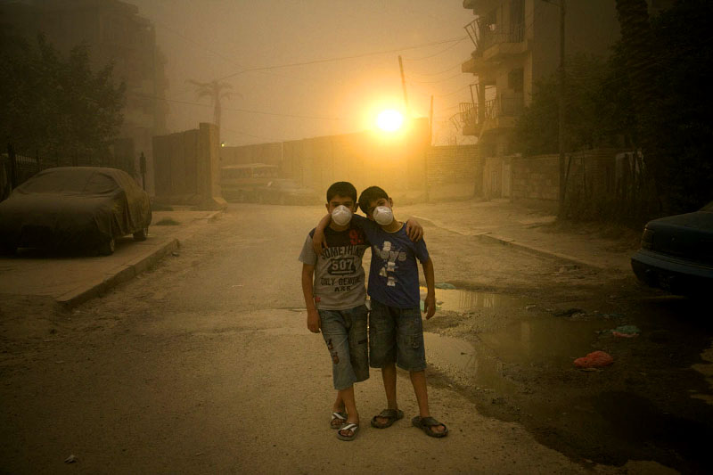 The dust smells like chalk. Heavy and still, the air is orange-tinted. Breathable until it hits your chest, causing a stuttering cough.In the Karrada neighborhood of Baghdad, Hussein Abbas, 10, and Zaid Alaa, 12, head first to a pharmacy for surgical masks. Cousins, but more like brothers. Inseparable best friends, looking for any opportunity to go outside, even during dust storms.Kicking rocks and avoiding puddles of sewage, they have been sent to find a nurse who lives in an apartment a few blocks away. Zaid's sister is sick with the flu and needs medicine.At a maze-like checkpoint for cars, an Iraqi guard ruffles Zaid's dust-grayed hair. From there, the boys can see an abandoned house with balconies torn like twisted metal combs. Three years ago, the windows in Hussein's home were shattered by the force of two suicide bombs that exploded, minutes apart, a few houses down from where he lives.Zaid lived in a different neighborhood at the time. A Sunni group took his home, he says, and now his family lives here in Karrada, a largely Shiite neighborhood. The move was a good thing, Hussein says. His cousin is now his neighbor.Farther down their cluttered, dead-end street, they pass through a tunnel of blast walls. In adrenaline-rushed voices, Zaid and Hussein brag about their favorite players on Iraq's national soccer team, Younis Mahmoud and Hawar Mulla Mohammed.The street is brown, even without the dust. Trash provides the only color. The storm is getting worse. In 10 steps, people disappear into the thickening air.The boys approach the apartment building and realize the streetlights are on. Their skinny legs begin to move faster, up the steps. Hussein's parents have rules, strictly enforced since the double bombing. They must stay in the neighborhood, never walk alone and always come home before dark.