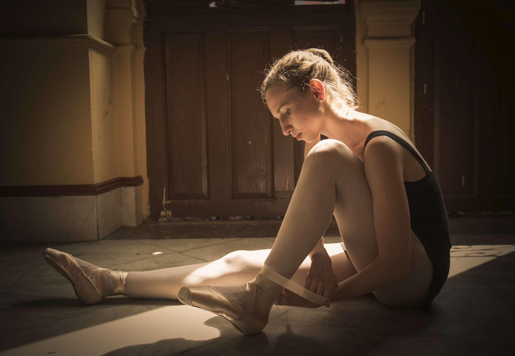 Catherine Conley laces up her pointe shoes prior to class at the Cuban National School of Ballet in Havana, March 13, 2017. ©2018 Alex Garcia
