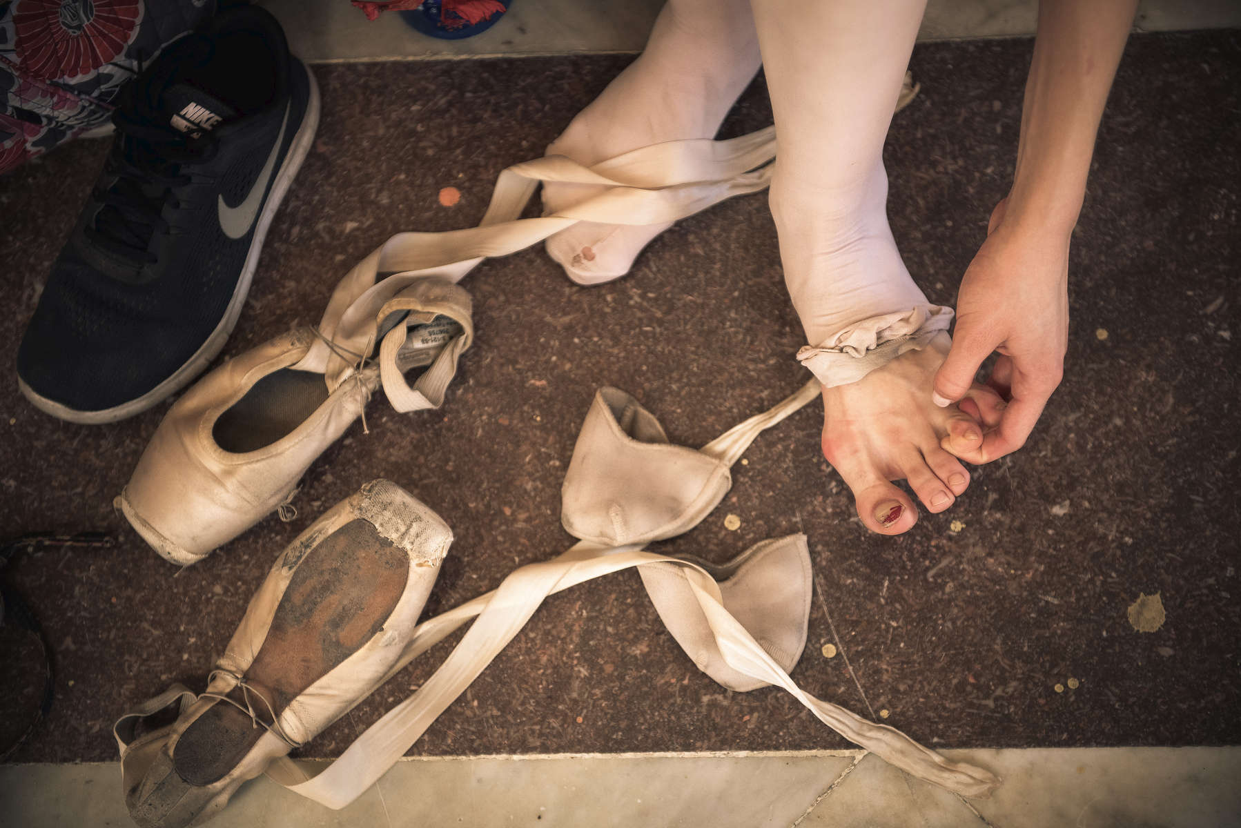 Catherine Conley tends to her feet after removing her pointe shoes after class at the Cuban National School of Ballet in Havana, March 10, 2017. ©2018 Alex Garcia