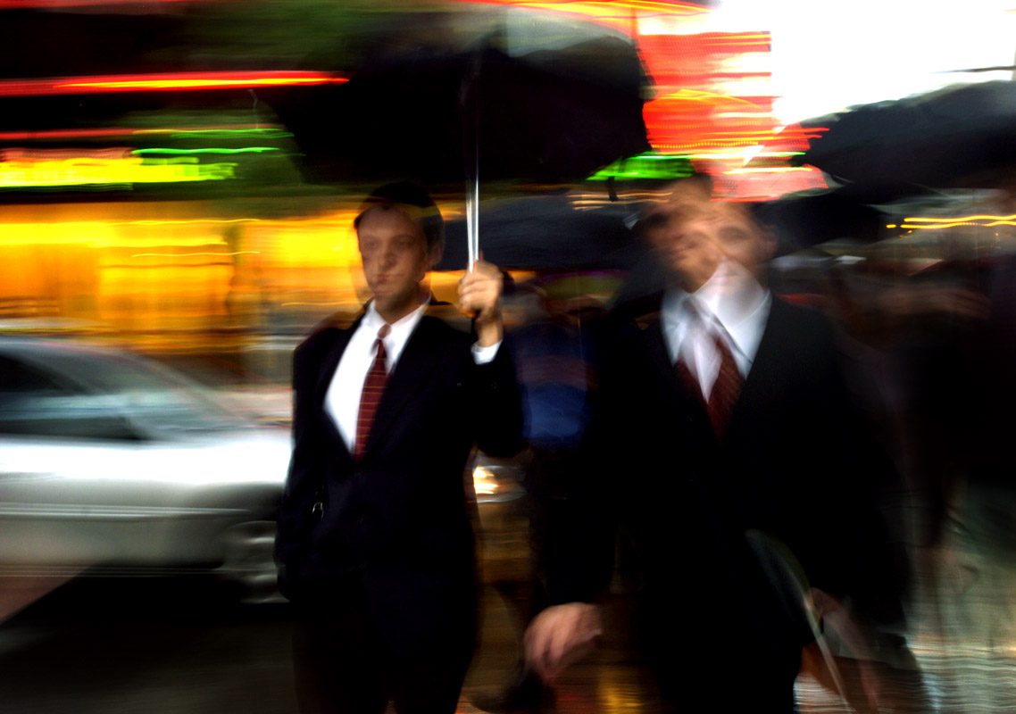 Businessmen during the rain in the financial district of Chicago.