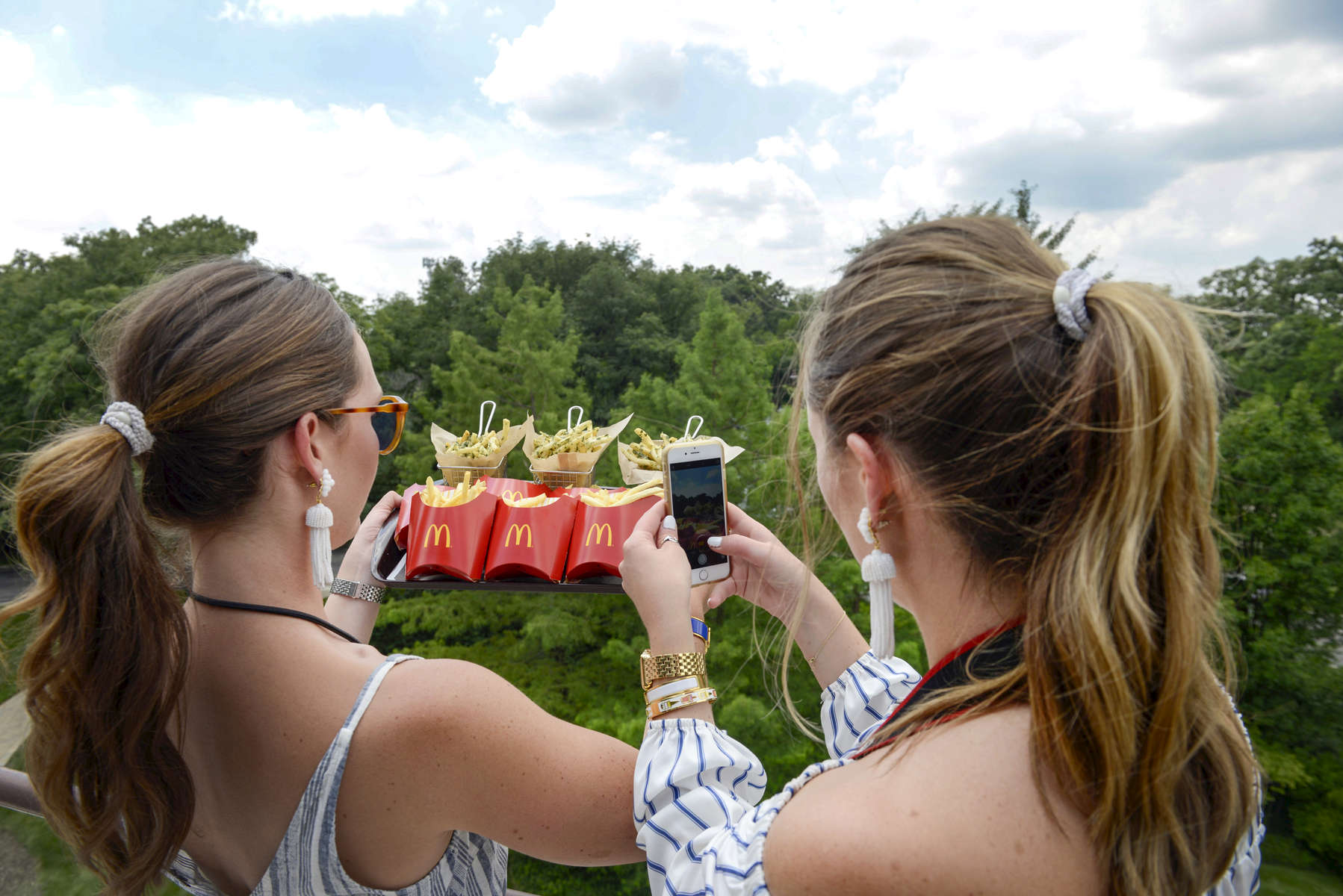Carolyn Niemann, left, and her sister Meg Niemann of @foodintheair snap a picture of McDonald's World Famous Fries next to Gilroy Garlic Fries at a food event at McDonald's headquarters on Monday, Aug. 1, 2016, in Oak Brook, Ill.(Alex Garcia/AP Images for McDonald's)