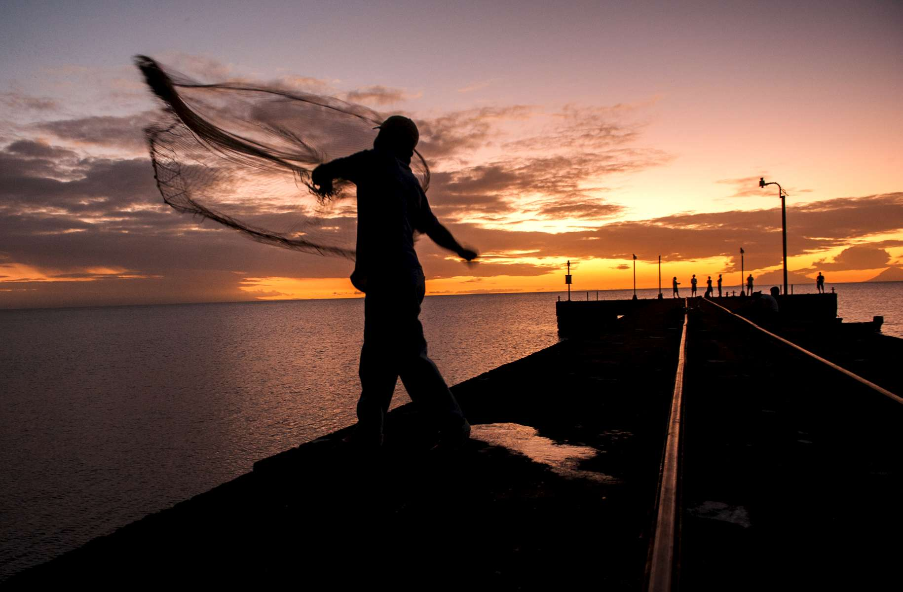 Fishing in Lake Nicaragua, Martin Correa throws out a net at sunset from at pier at San Miguelito.