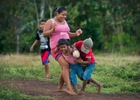 Women and children of Bangkukuk regularly play stickball in an open field in the village while the men of the village are away during the day.