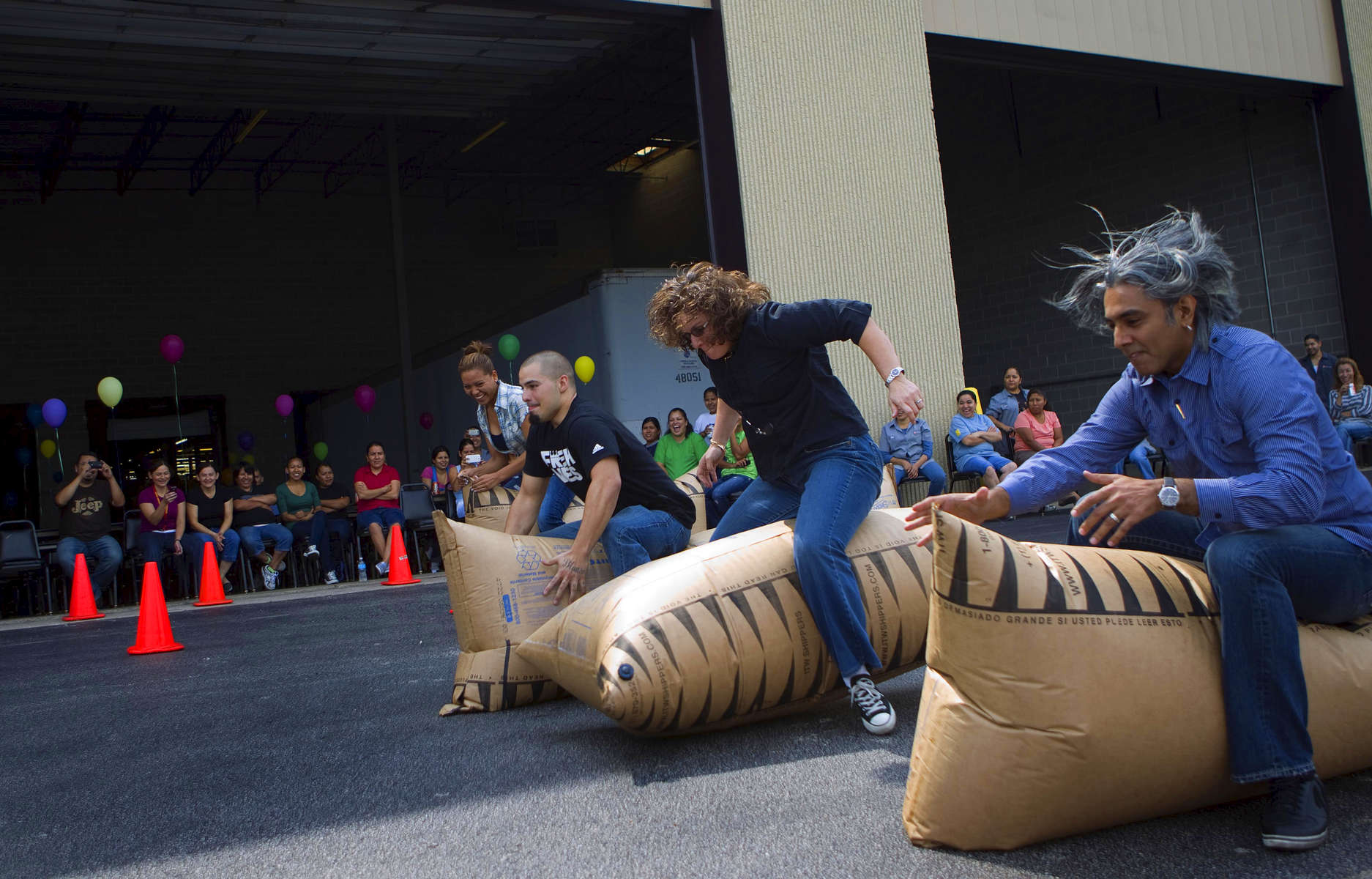 Employees hop on inflated bags during a company picnic festivities at the iD Commerce headquarters.