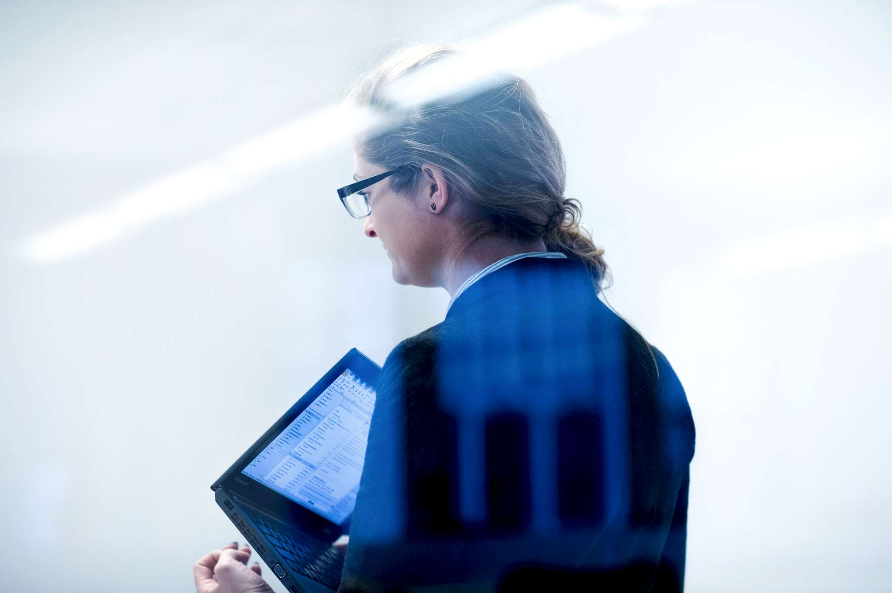 A woman holding a laptop during a meeting at a corporation.