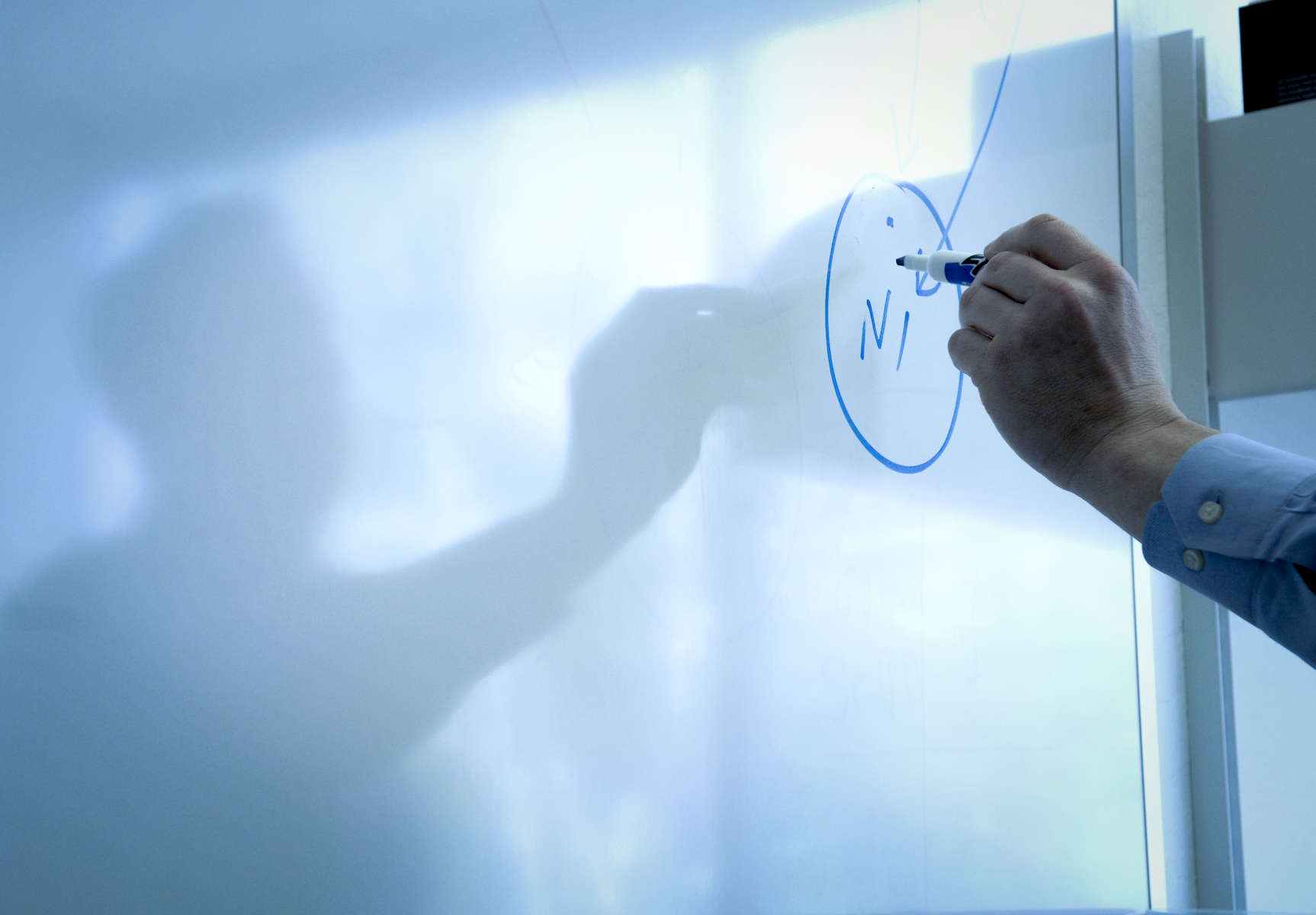 A hand and shadow of a man writing on a white board at a corporation.