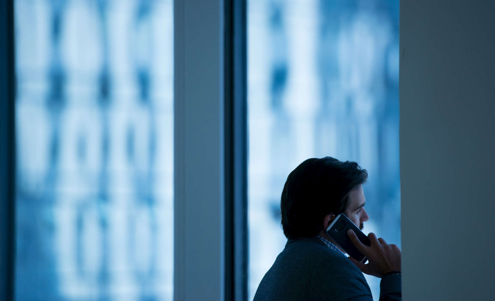 A man talking on a phone at a technology consulting firm in Chicago.