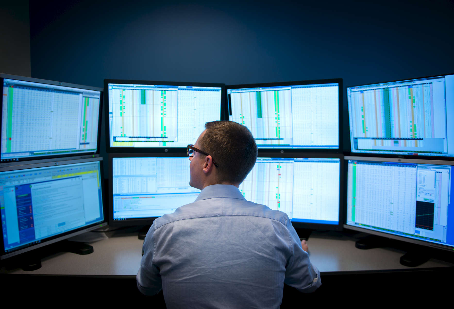A trader sits in front of monitors at a corporate trading firm.