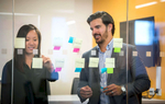 Photograph of two people using sticky notes on a glass wall at a corporate office.