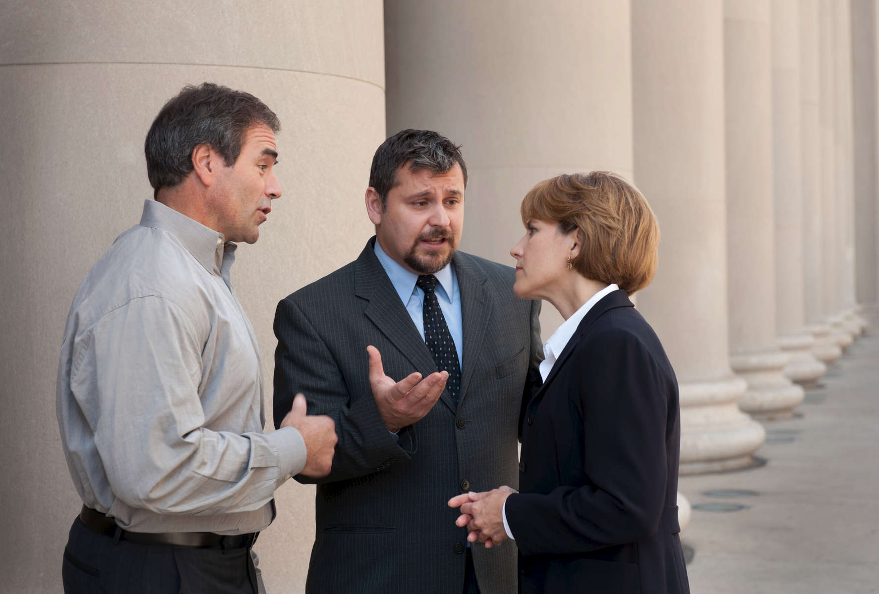 Corporate translator speaking to two people outside a courthouse.