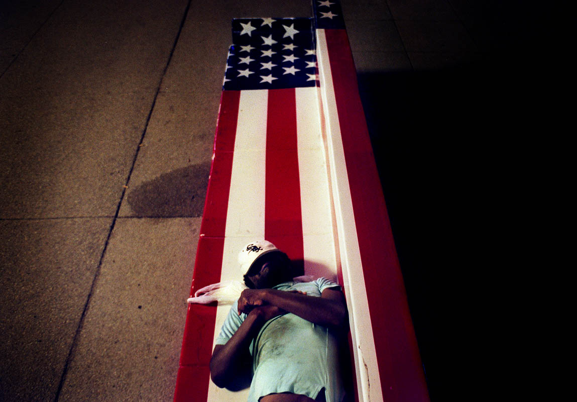 A homeless person sleeps on a bench that was part of a public art exhibit.